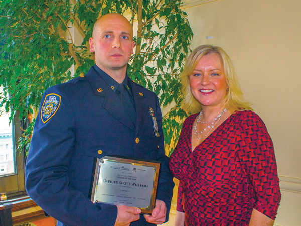 Photo by Zach Williams NYC Community Media publisher Jennifer Goodstein, with NYPD Officer Scott Williams of the 10th Precinct (holding his Officer of the Year award). Williams played a key role in the arrest of two foreign nationals who were using the identities of 53 different individuals to withdraw money from local ATMs.