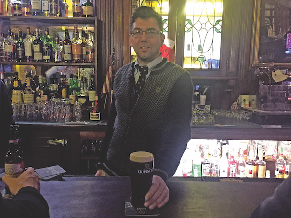 Fourth-generation Peter McManus Café owner Justin McManus serves up a well-poured Guinness. File photo by Dennis Lynch.