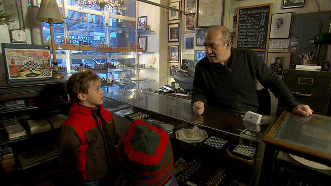 Chess Forum owner Imad Khachan talks shop with Oliver Armstrong, 8 and his brother Henry, 6.